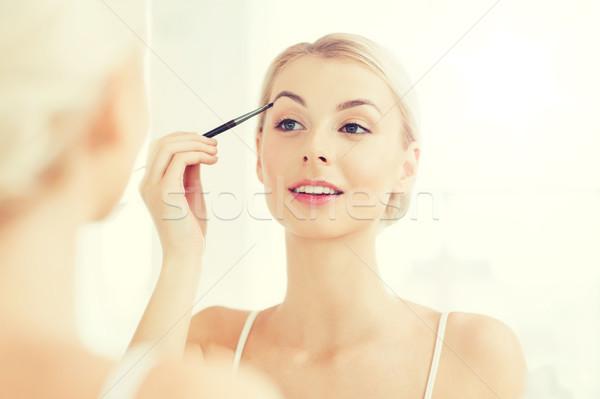 Kobieta szczotki brew makijaż łazienka piękna Zdjęcia stock © dolgachov
