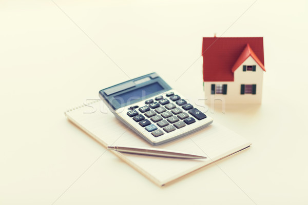 close up of home model, calculator and notebook Stock photo © dolgachov