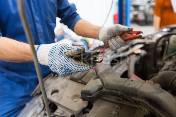 auto mechanic man with cleats charging battery Stock photo © dolgachov
