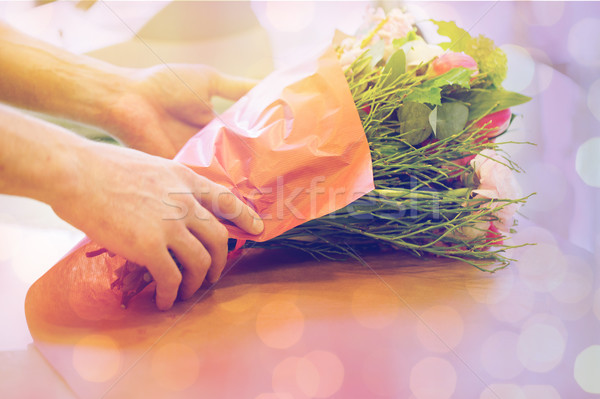florist wrapping flowers in paper at flower shop Stock photo © dolgachov