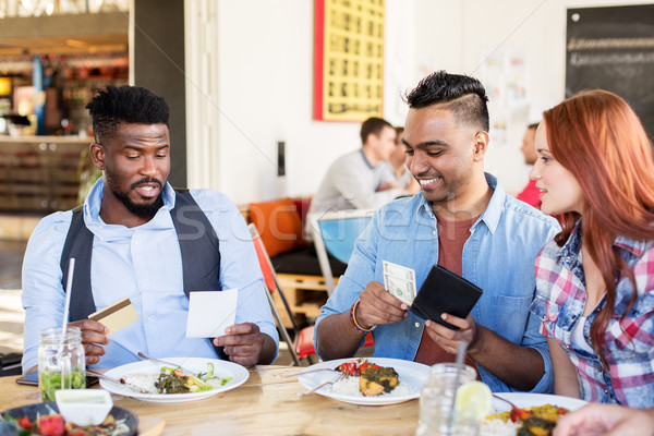 happy friends paying bill for food at restaurant Stock photo © dolgachov