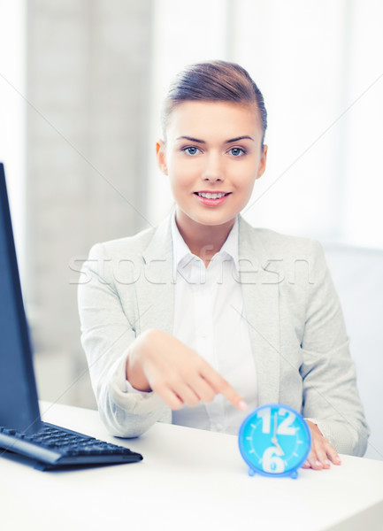 attractive businesswoman pointing at clock Stock photo © dolgachov