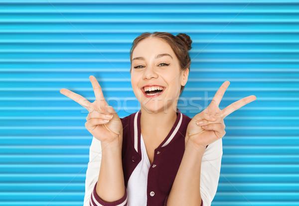 happy smiling teenage girl showing peace sign Stock photo © dolgachov