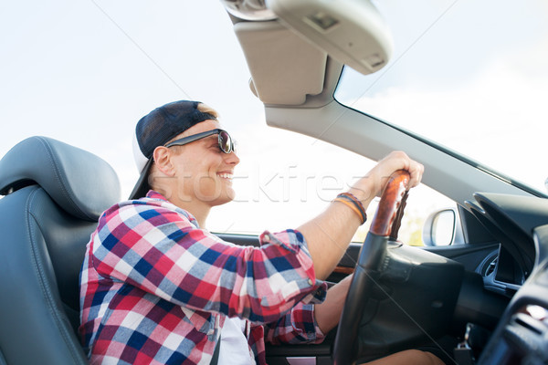 happy young man driving convertible car Stock photo © dolgachov