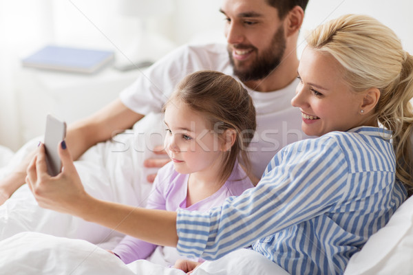 Stock photo: happy family taking selfie by smartphone at home