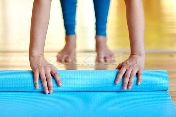 woman hands rolling yoga mat at gym or studio Stock photo © dolgachov