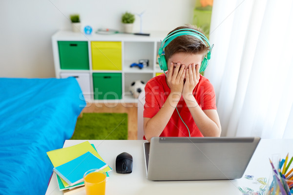 boy in headphones playing video game on laptop Stock photo © dolgachov