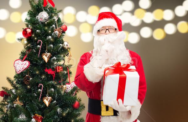 santa claus with gift box at christmas tree Stock photo © dolgachov