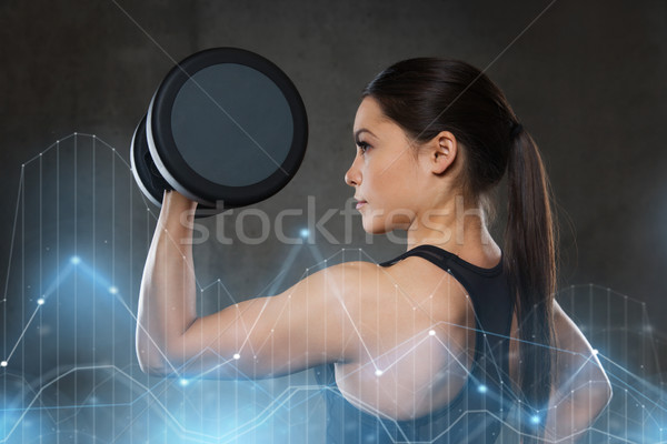 young woman flexing muscles with dumbbells in gym Stock photo © dolgachov