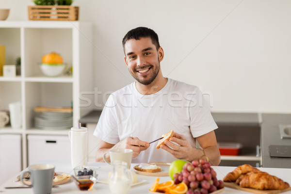 man eating toast with coffee at home kitchen Stock photo © dolgachov