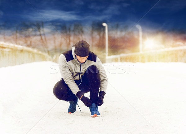 man with earphones tying sports shoe in winter Stock photo © dolgachov