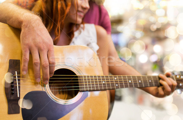 Stock photo: close up of couple playing guitar over lights