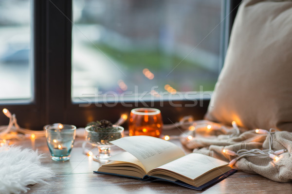 book, garland lights and candles on window sill Stock photo © dolgachov