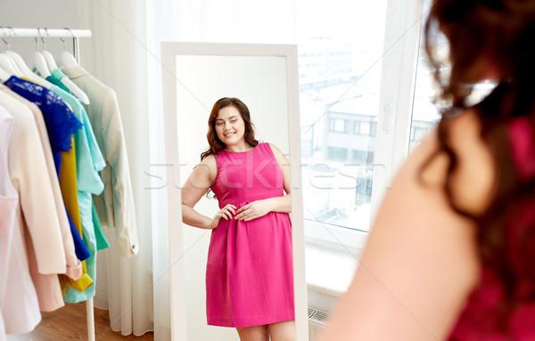 Szczęśliwy plus size kobieta sukienka patrząc lustra Zdjęcia stock © dolgachov