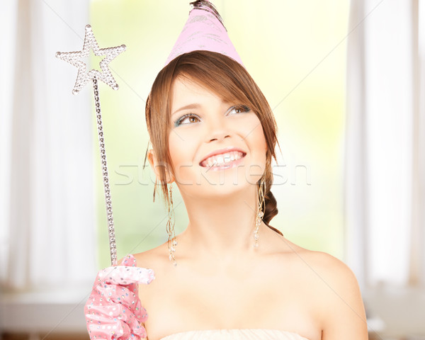 girl in party cap with magic wand Stock photo © dolgachov