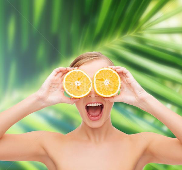amazed young woman with orange slices Stock photo © dolgachov