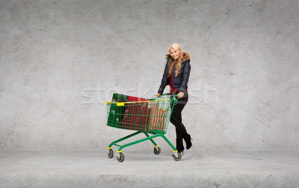 smiling woman in winter clothes with shopping car Stock photo © dolgachov