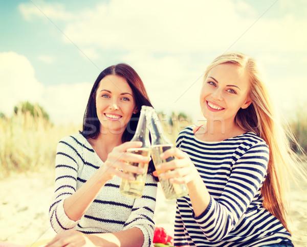 Barátnők üvegek sör tengerpart nyár ünnepek Stock fotó © dolgachov