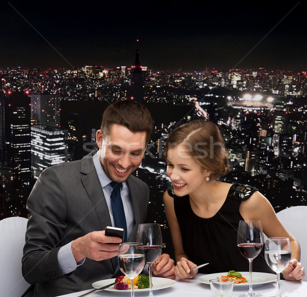 Gülen çift yeme restoran teknoloji Stok fotoğraf © dolgachov