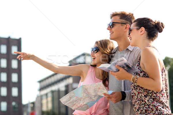 smiling friends with map and city guide outdoors Stock photo © dolgachov