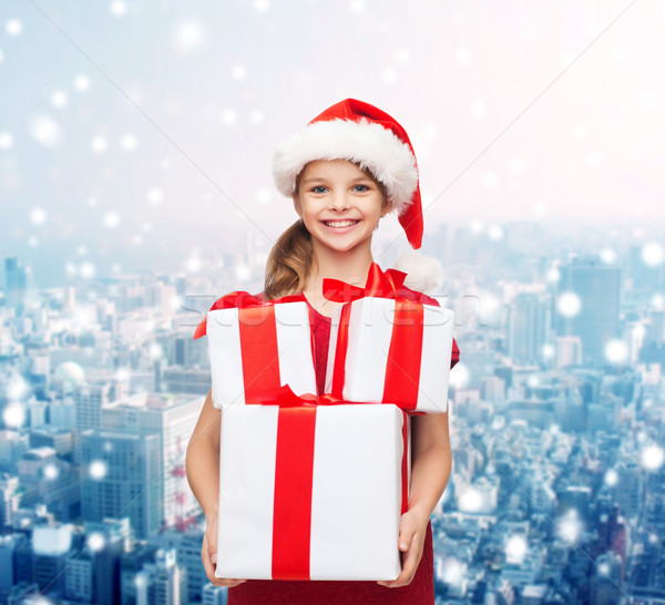 smiling little girl in santa helper hat with gifts Stock photo © dolgachov