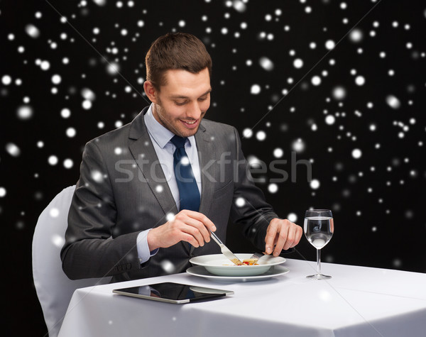 smiling man with tablet pc eating main course Stock photo © dolgachov