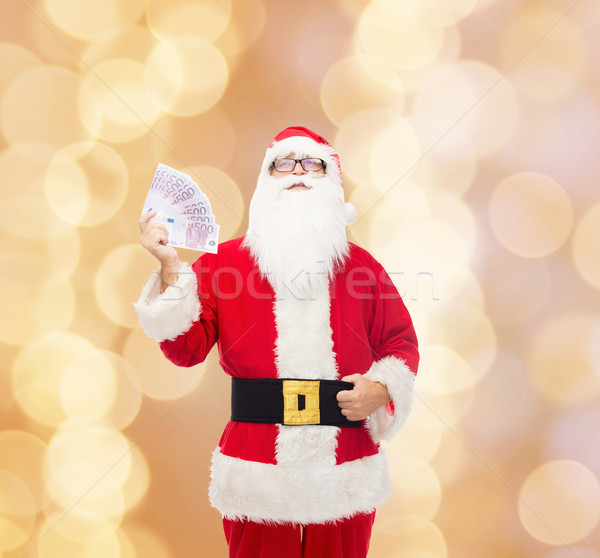 man in costume of santa claus with euro money Stock photo © dolgachov