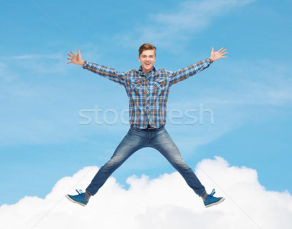 Uśmiechnięty młody człowiek skoki powietrza szczęścia wolności Zdjęcia stock © dolgachov