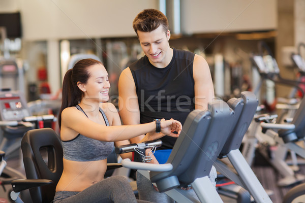 Stock photo: happy woman with trainer on exercise bike in gym