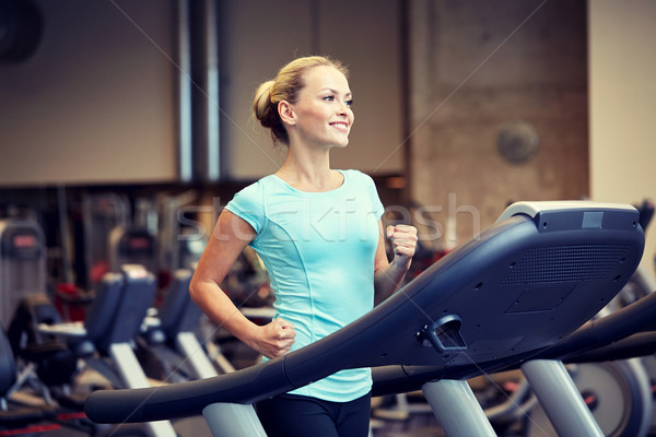 smiling woman exercising on treadmill in gym Stock photo © dolgachov