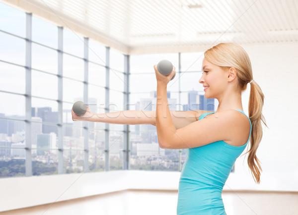 Mosolygó nő súlyzók bicepsz tornaterem fitnessz sport Stock fotó © dolgachov