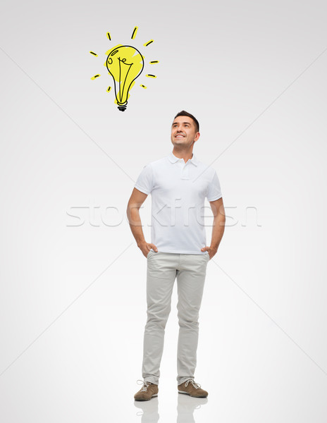 Souriant homme éclairage ampoule bonheur Photo stock © dolgachov