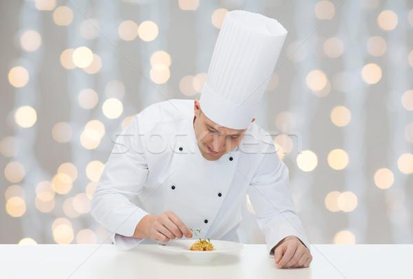 happy male chef cook decorating dish Stock photo © dolgachov
