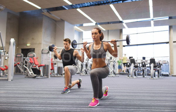 young man and woman training with barbell in gym Stock photo © dolgachov