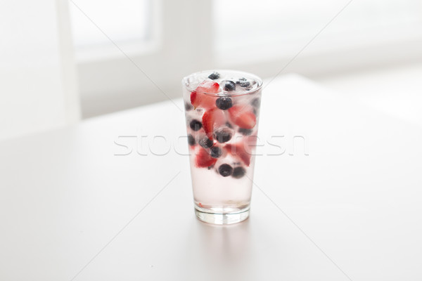 close up of fruit water with ice cubes in glass Stock photo © dolgachov