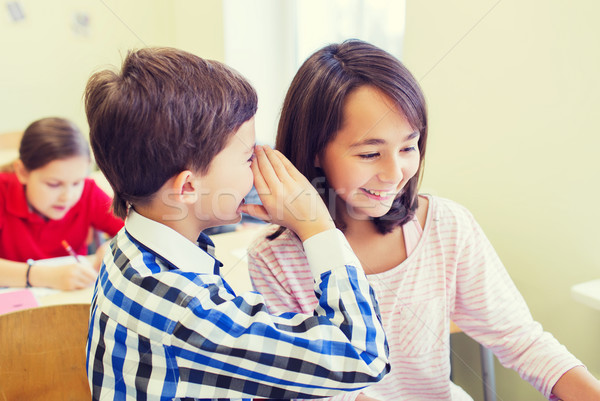 Stock photo: smiling schoolboy whispering to classmate ear