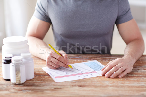 close up of man with protein jars and diet plan Stock photo © dolgachov