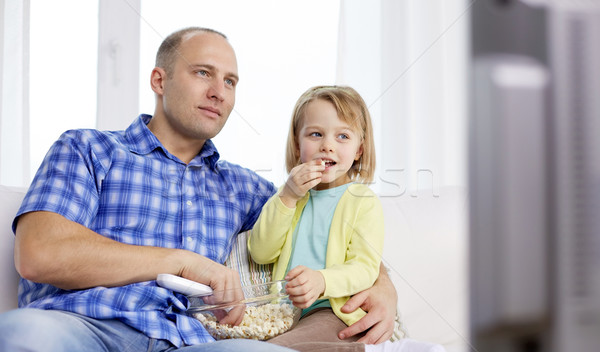 happy family with popcorn watching tv at home Stock photo © dolgachov