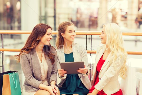 Boldog fiatal nők táblagép bevásárlótáskák vásár fogyasztói társadalom Stock fotó © dolgachov