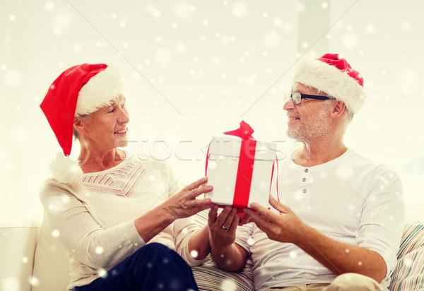 happy senior couple in santa hats with gift box Stock photo © dolgachov