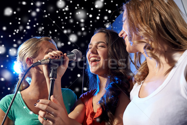 Stock photo: happy young women singing karaoke in night club