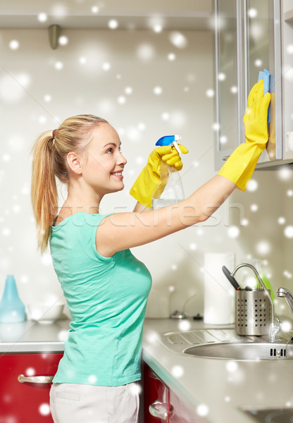 happy woman cleaning cabinet at home kitchen Stock photo © dolgachov