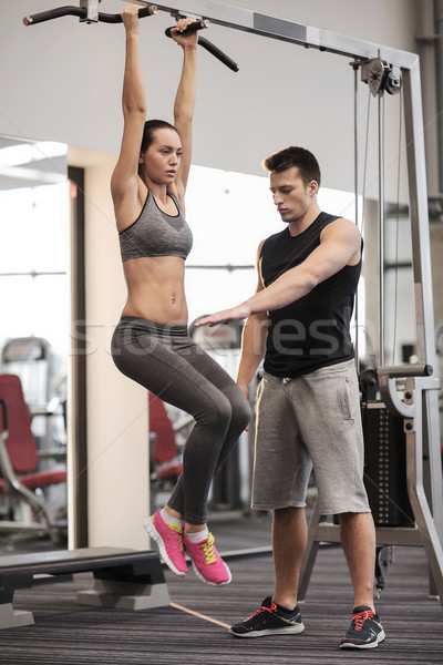 young woman with trainer doing leg raises in gym Stock photo © dolgachov