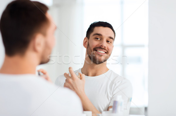 Homem perfume olhando espelho banheiro perfumaria Foto stock © dolgachov