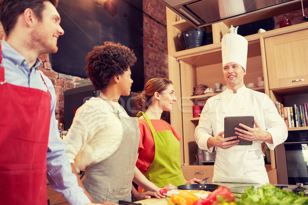 happy friends with tablet pc in kitchen Stock photo © dolgachov
