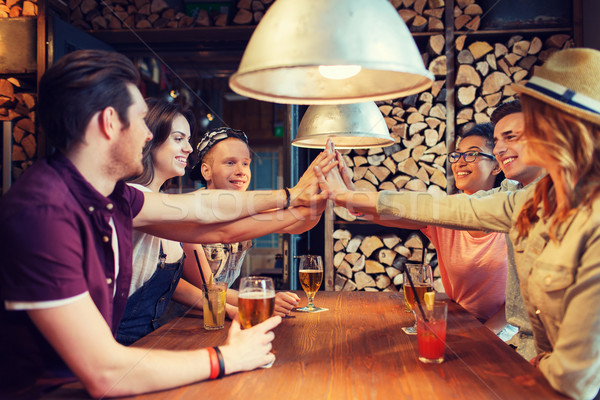 happy friends with drinks making high five at bar Stock photo © dolgachov