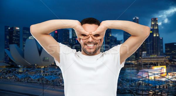man making finger glasses over city background Stock photo © dolgachov