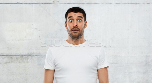scared man in white t-shirt over wall background Stock photo © dolgachov