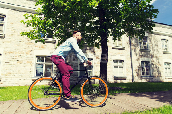 Stock photo: happy young hipster man riding fixed gear bike