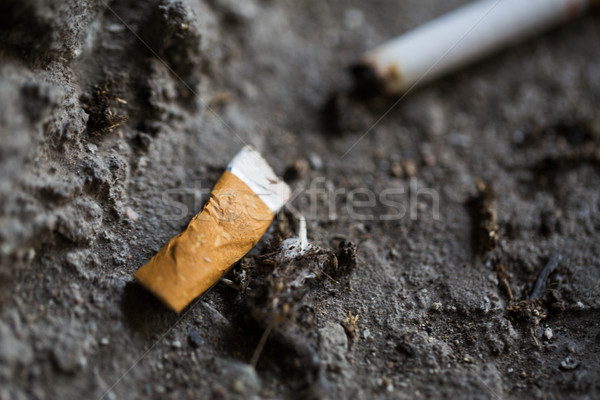 Stock photo: close up of smoked cigarette butt on ground